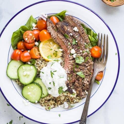 easy mediterranean steak and quinoa bowl topped with tzatziki