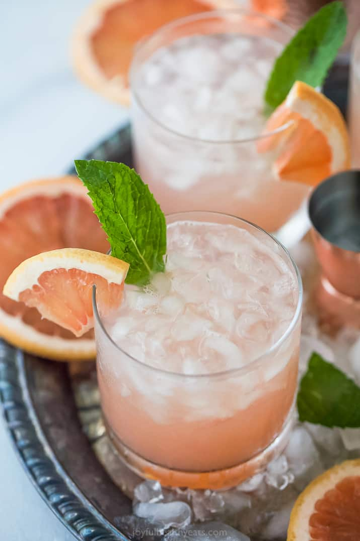 salty dog cocktail in two glasses garnished with mint and grapefruit slices