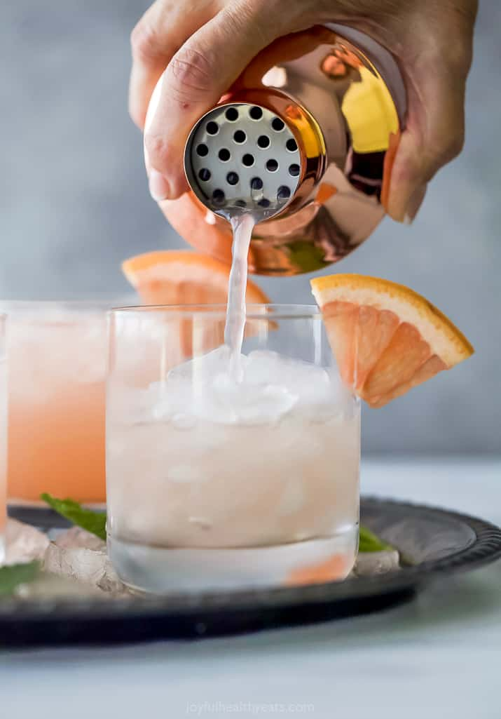 pouring homemade salty dog cocktail into a glass of ice