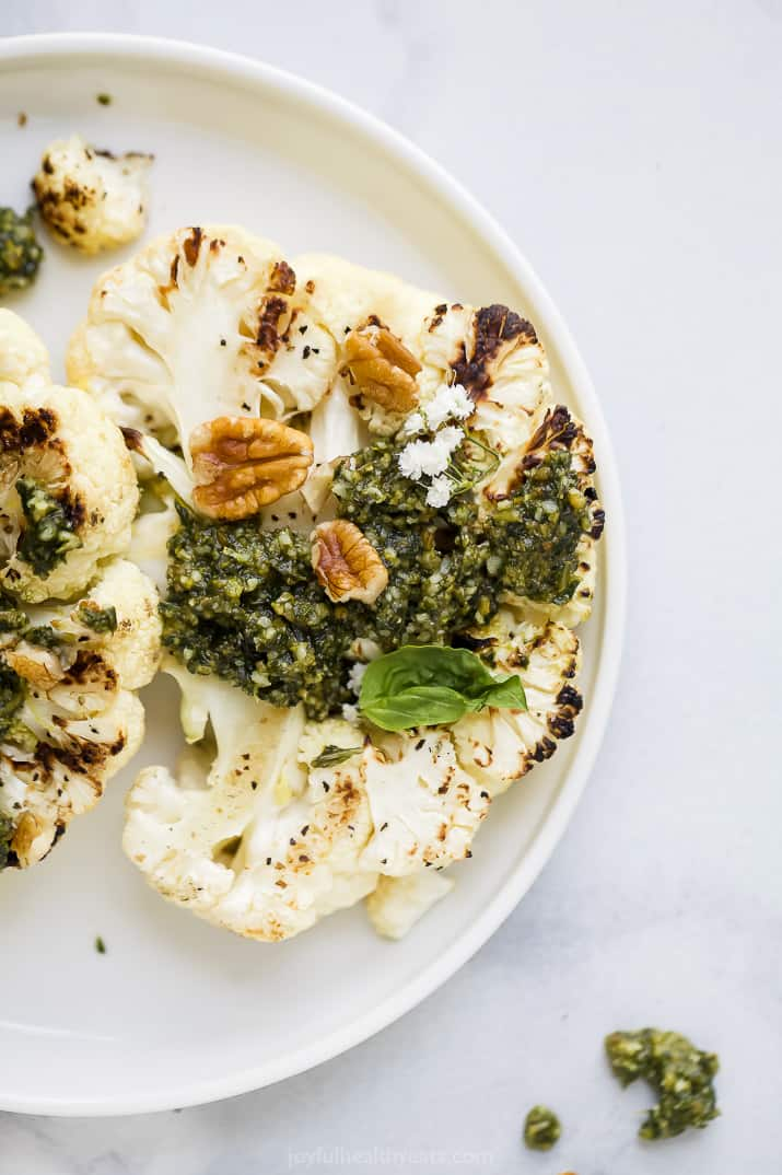 grilled cauliflower steaks with basil pecan pesto on a plate