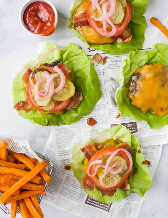 overhead photo of keto bacon cheeseburgers on a lettuce cup with sweet potato fries