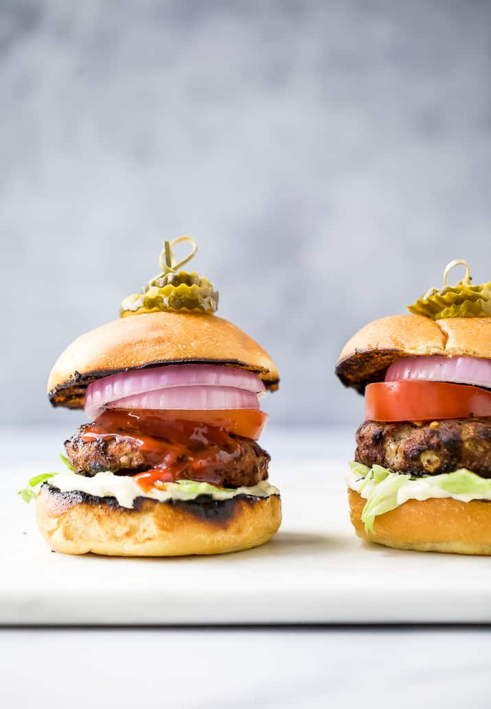 the ultimate classic turkey burgers on a cutting board with all the toppings