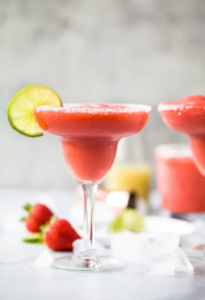 side photo of the ultimate frozen strawberry margaritas in a glass with a lime on the rim