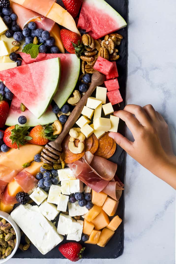overhead photo of summer cheese board with hand grabbing food