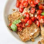 a bunch of pecan crusted tilapia with tomato bruschetta on a plate with fresh basil