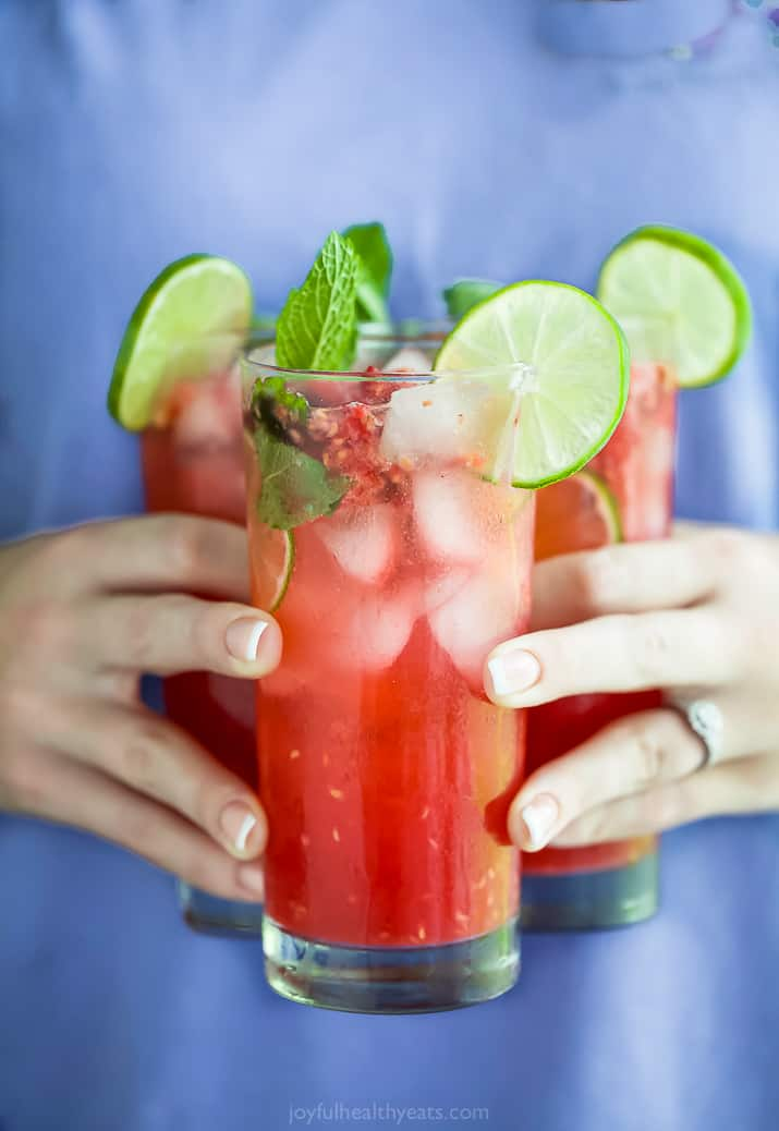 hands holding three glasses filled with the best fresh raspberry mojito recipe