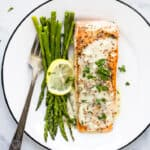 pan seared salmon drizzled with creamy dijon sauce on a plate