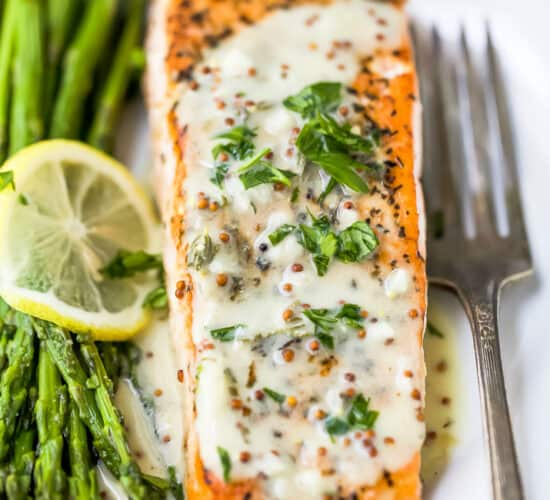 close up photo of pan seared salmon drizzled with creamy dijon sauce on a plate with asparagus