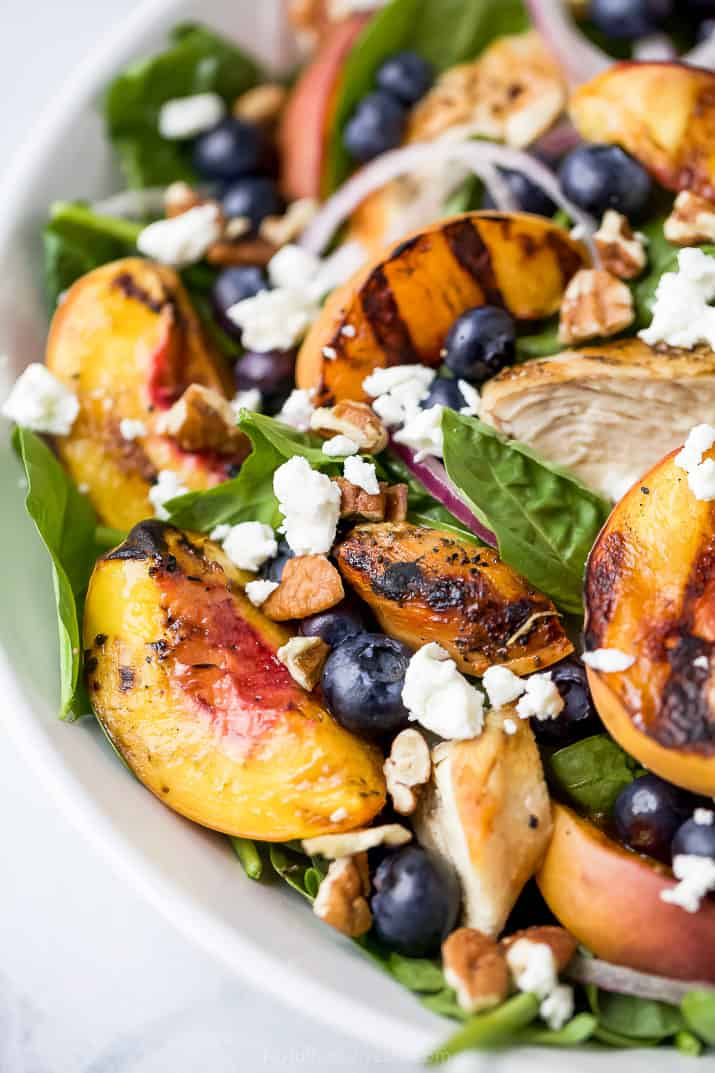 close up photo of grilled peach chicken salad in a bowl