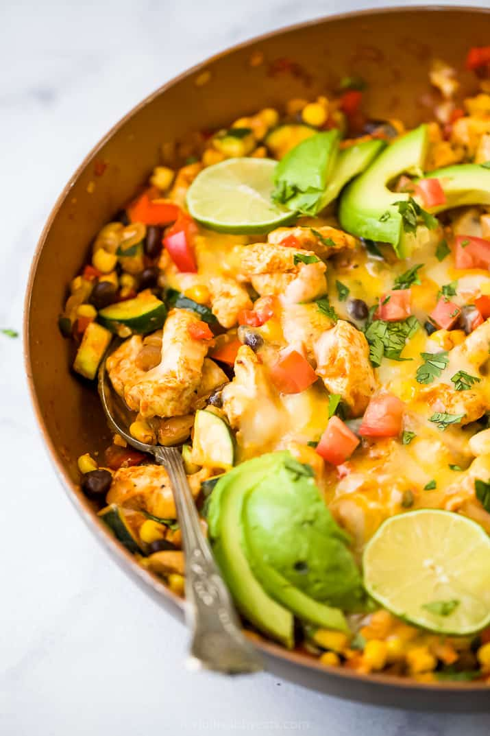 closeup side photo of 30 minute zucchini chicken enchilada skillet in a pan topped with avocado