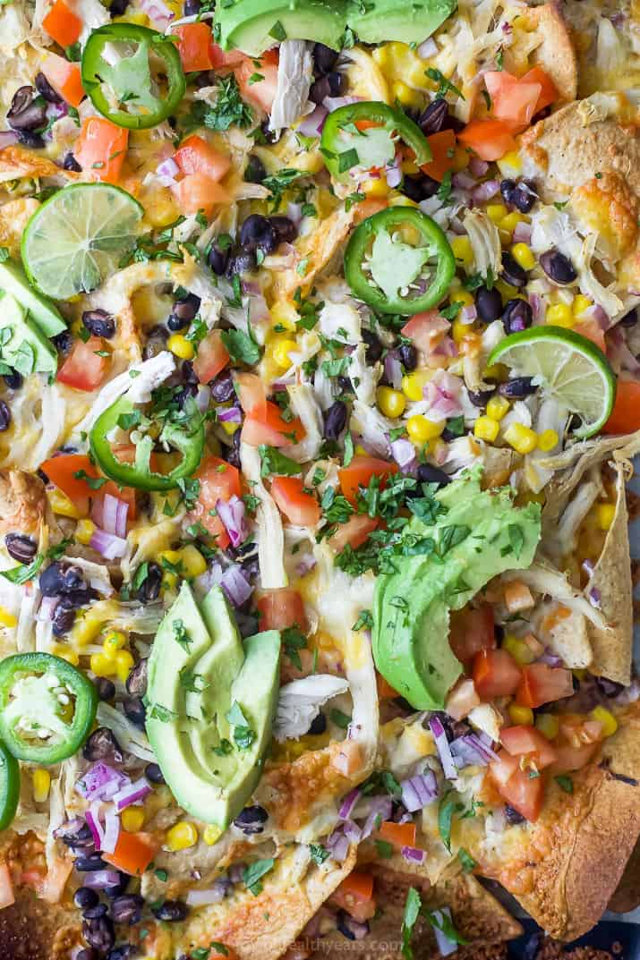 overhead photo of easy 20 minute sheet pan chicken nachos topped with avocado