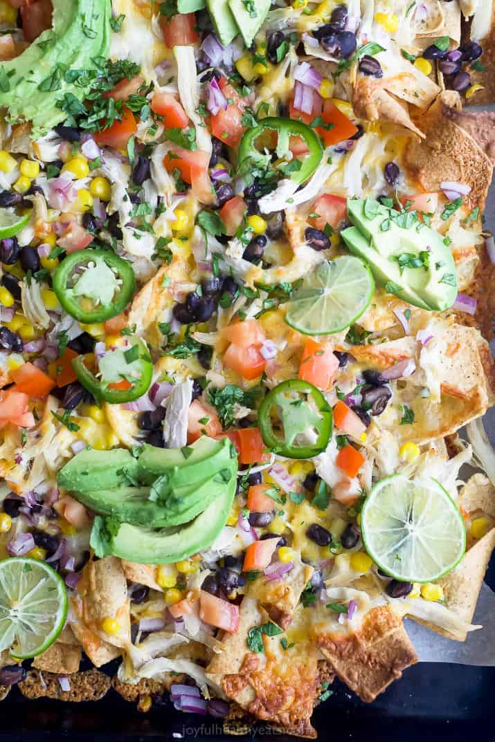 easy 20 minute sheet pan chicken nachos topped with avocado