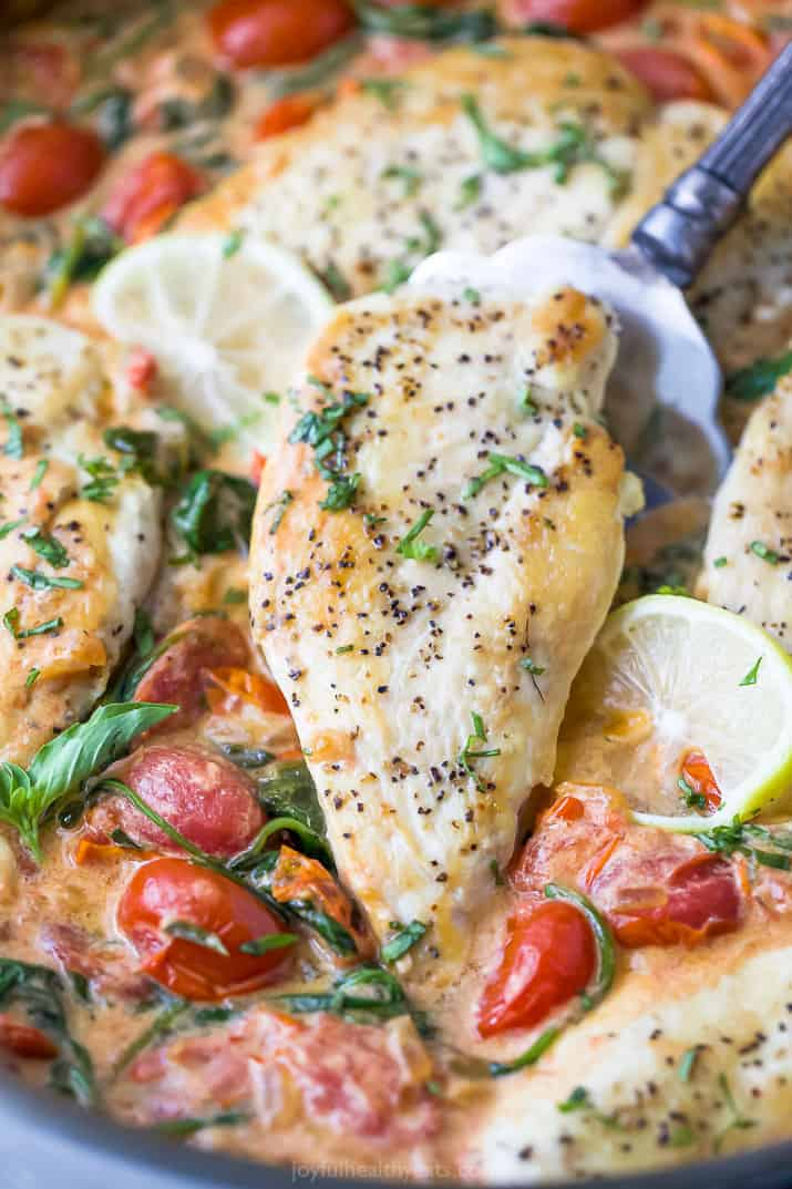 easy 30 minute creamy tuscan chicken with a spatula under the chicken