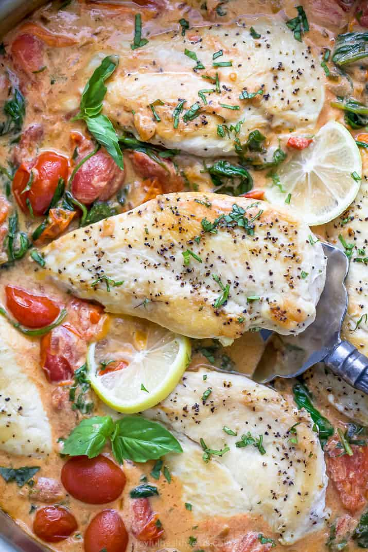 closeup photo of easy 30 minute creamy tuscan chicken in a pan with a spatula scooping