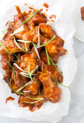 close up photo of baked sweet and spicy bbq chicken wings in a basket with green onions