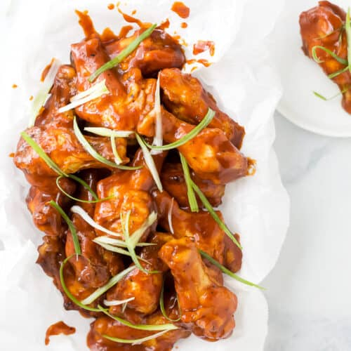 baked sweet and spicy bbq chicken wings in a basket with green onions