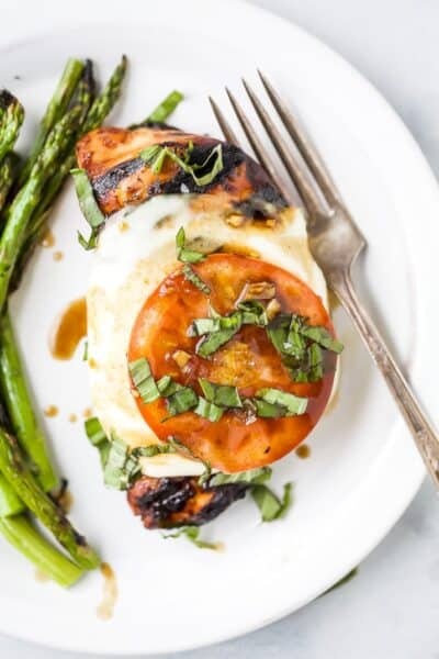 easy grilled balsamic caprese chicken on a plate with asparagus