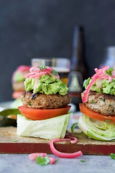 paleo chipotle turkey burgers with guacamole piled on a lettuce wedge