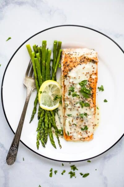 pan seared salmon with creamy dijon sauce on a plate with asparagus