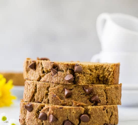 A stack of three pieces of pumpkin banana bread on a counter with two mugs in the background