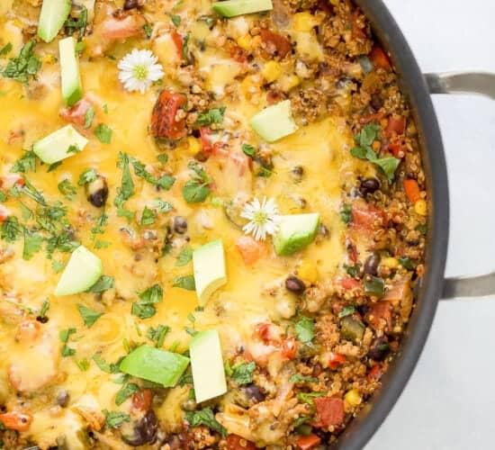 healthy one pan cheesy quinoa taco skillet topped with avocado