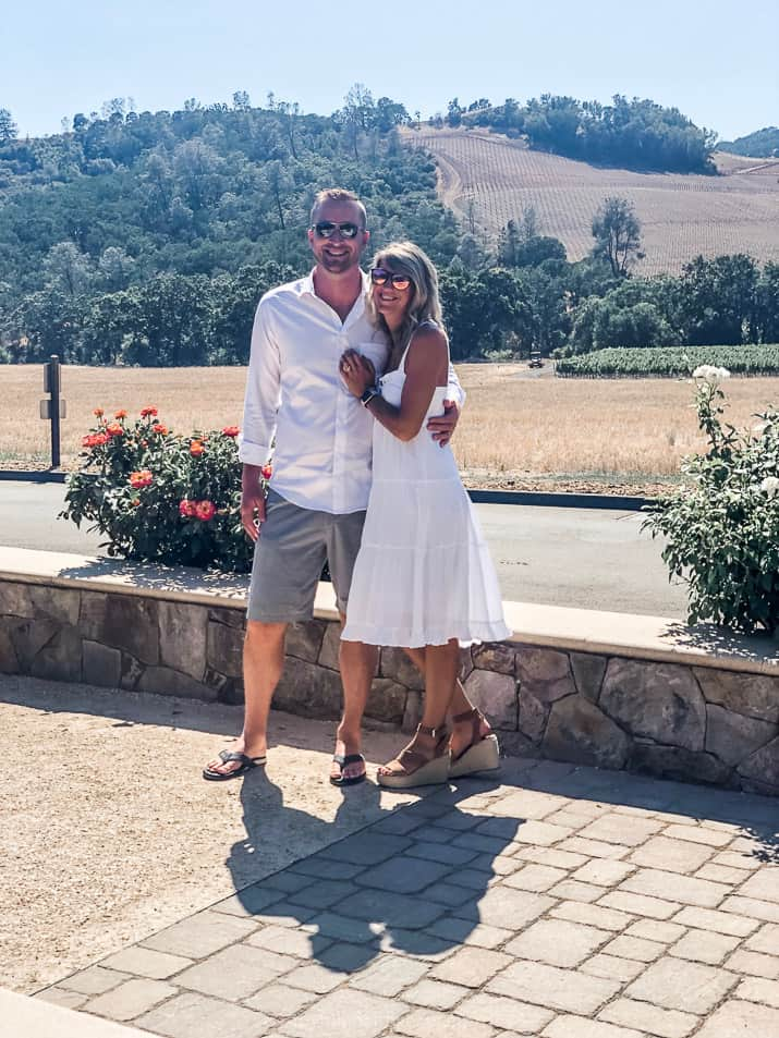 top 5 wineries in california's wine country - a couple taking a photo in front of a vineyard