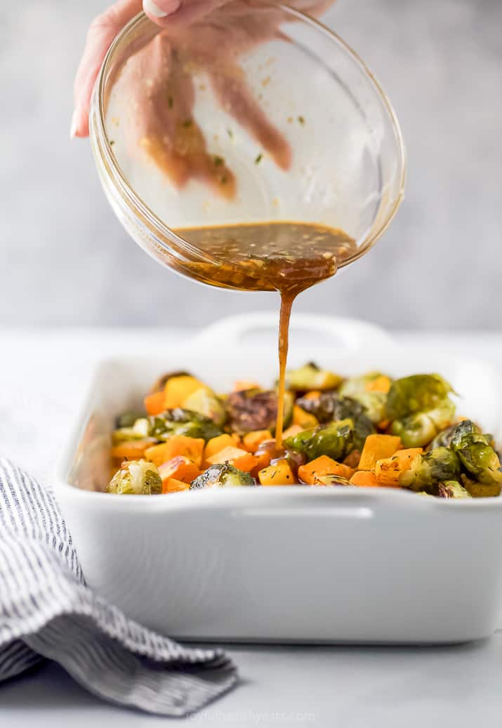 pouring dressing over roasted vegetables