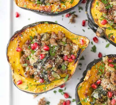 overhead photo of apple sausage stuffed acorn squash with pomegranate on top
