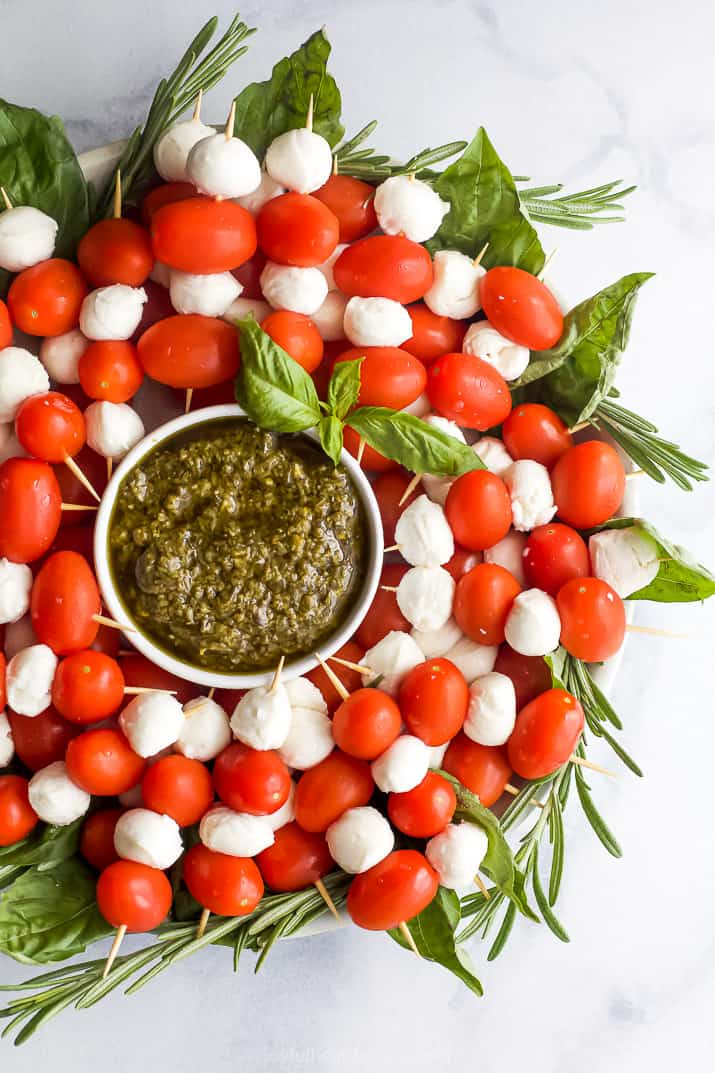 overhead photo of caprese skewer wreath with pesto sauce