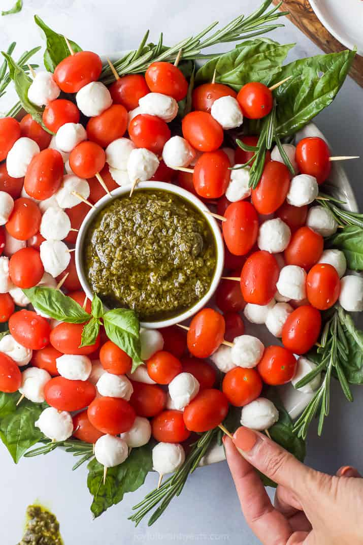 overhead photo of caprese skewers wreath with peso and a hand grabbing a skewer