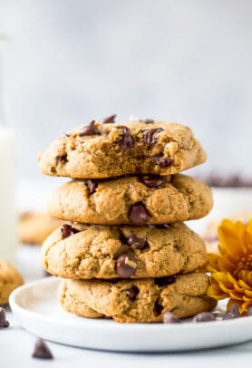 closeup photo of vegan pumpkin chocolate chip cookies stacked on top of each other
