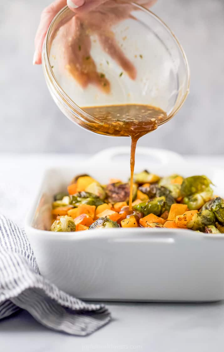 pouring maple dijon glaze over roasted butternut squash and brussel sprouts