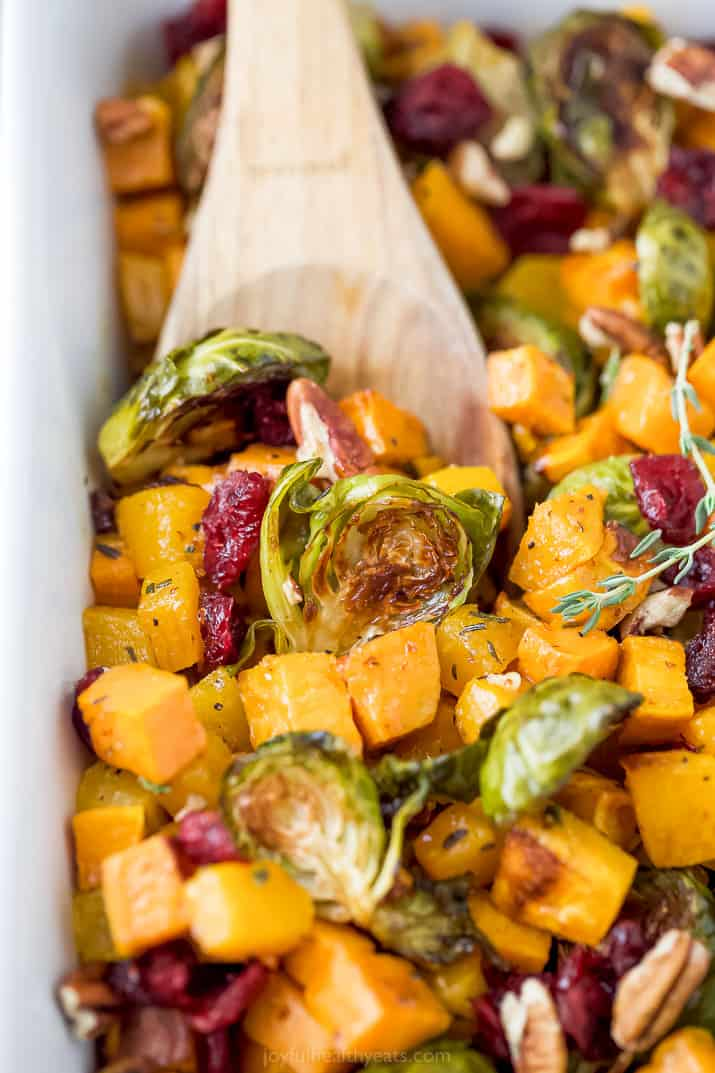 a wooden spoon scooping maple dijon roasted butternut squash brussel sprout salad