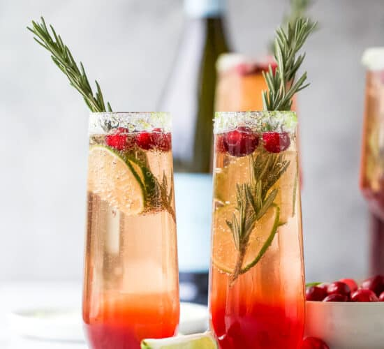 two side by side glasses filled with easy cranberry mimosa recipe with garnish