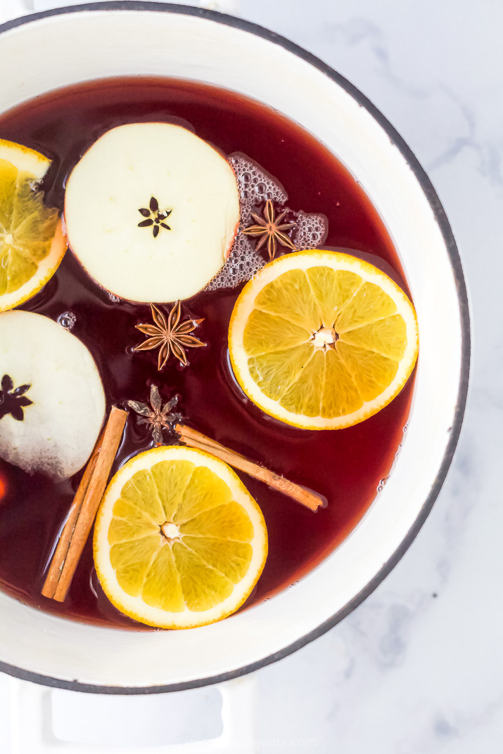 overhead photo of festive spiked cranberry mulled apple cider in a dutch oven