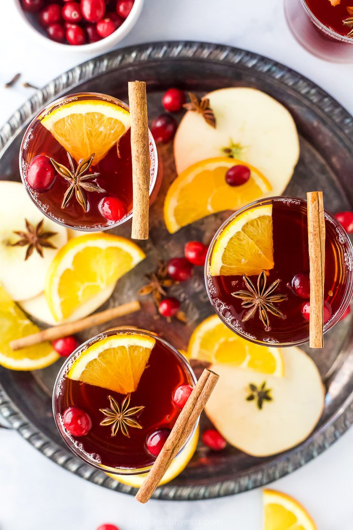 overhead photo of a glassed filled with spiked cranberry mulled apple cider