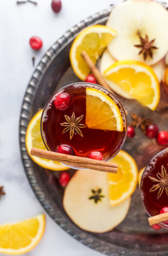 overhead photo of spiked cranberry mulled apple cider on a tray