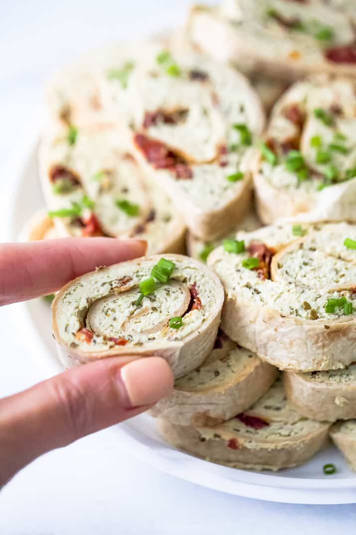 a hand taking one roll of a pesto chicken pinwheel