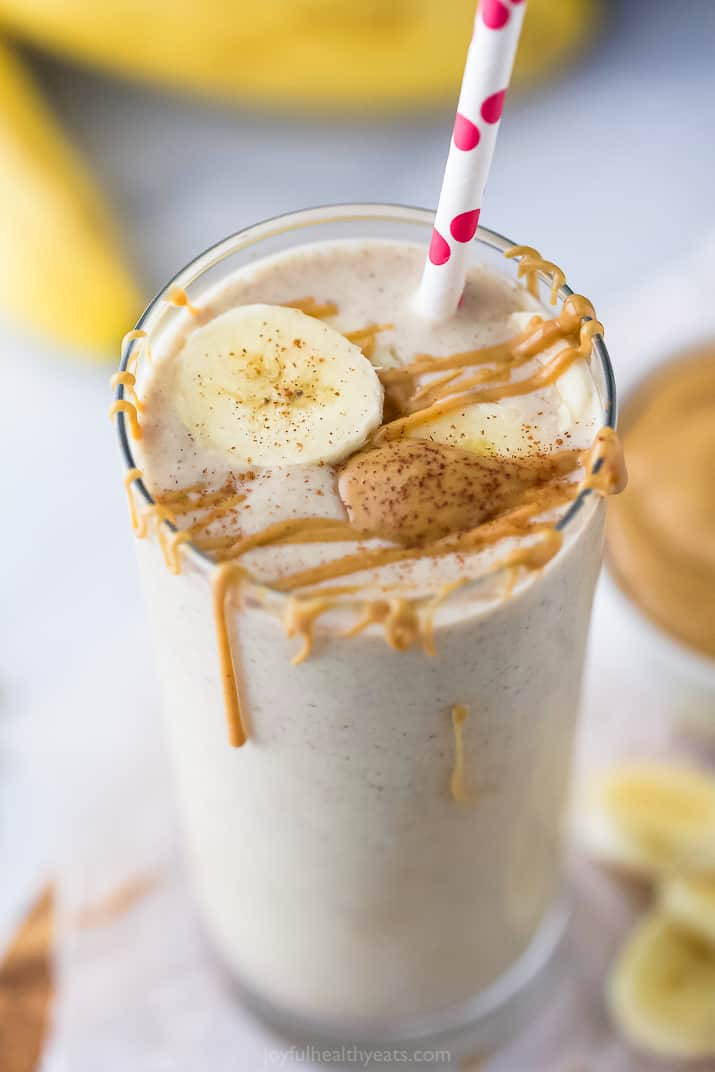 close up photo of creamy peanut butter banana smoothie with peanut butter drizzle