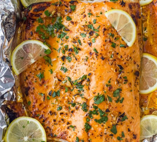 overhead photo of easy 20 minute garlic butter baked salmon in foil recipe with lemons on top