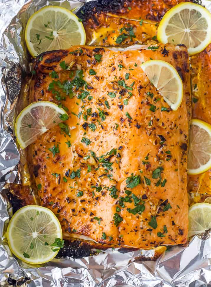 Cooked salmon in aluminum foil with lemon slices and herbs