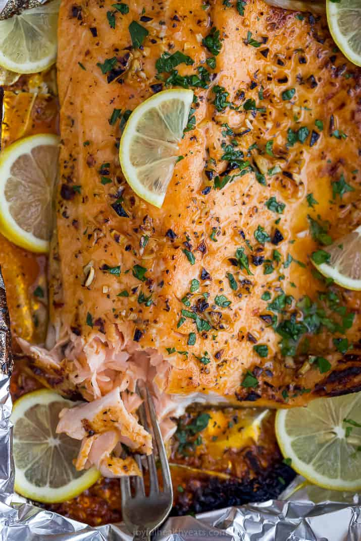 Flaky baked salmon with a fork in it, topped with lemon slices