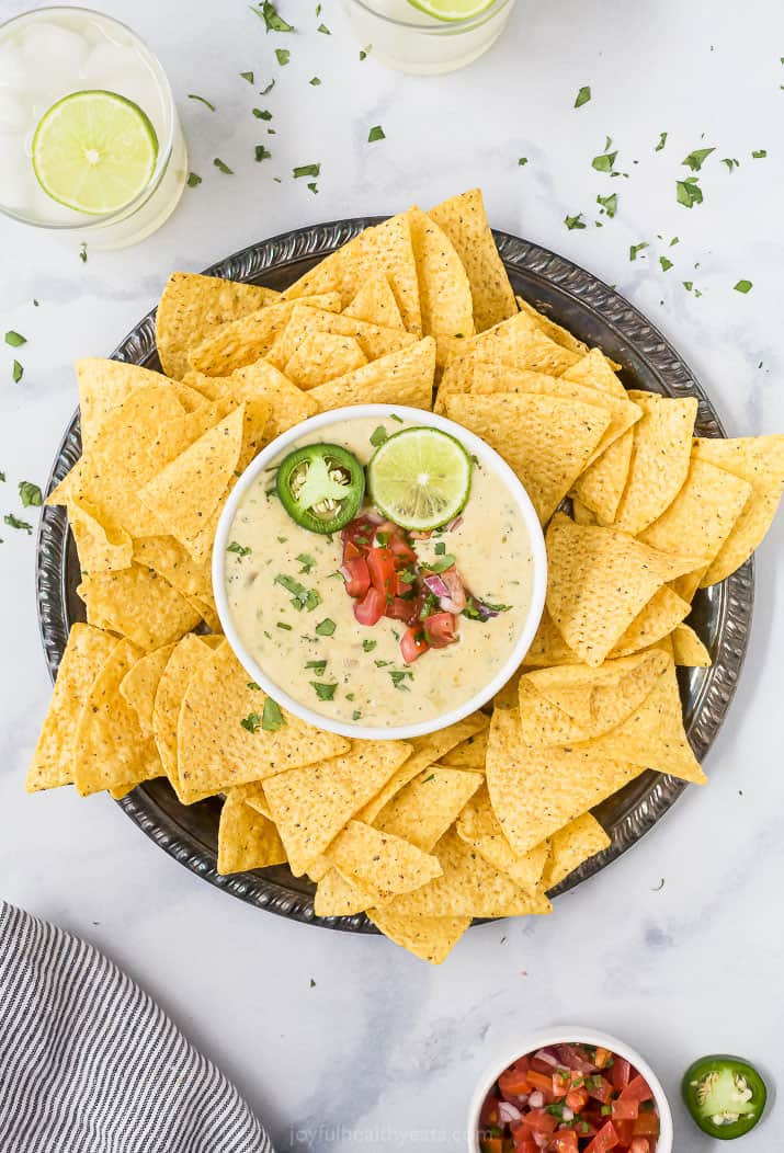 the perfect creamy white queso dip recipe on a tray with chips