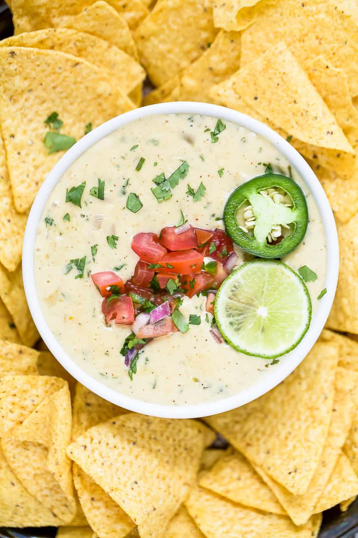 overhead photo of creamy white queso dip with chips around it