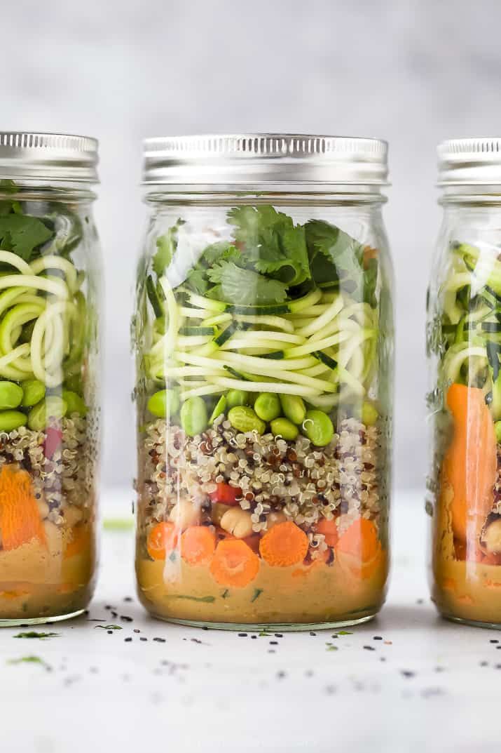 close up of crunchy vegetarian thai quinoa salad with peanut dressing in mason jars