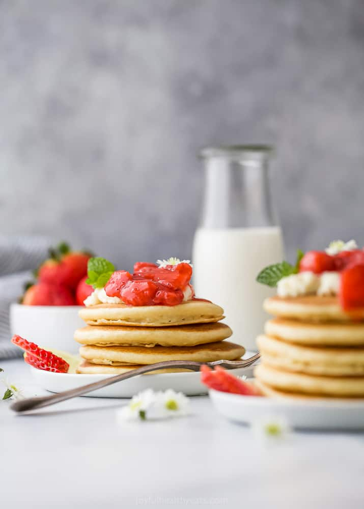 a stack of healthy fluffy pancakes with strawberry compote on top