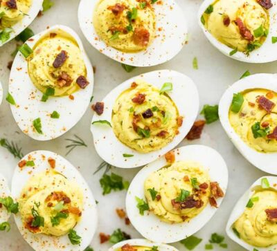 close up photo of classic deviled eggs recipe topped with bacon and chives
