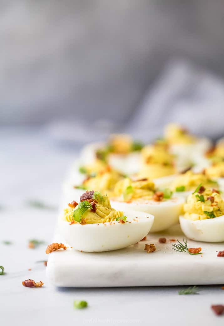 a side photo of classic deviled egg with bacon topped with chives