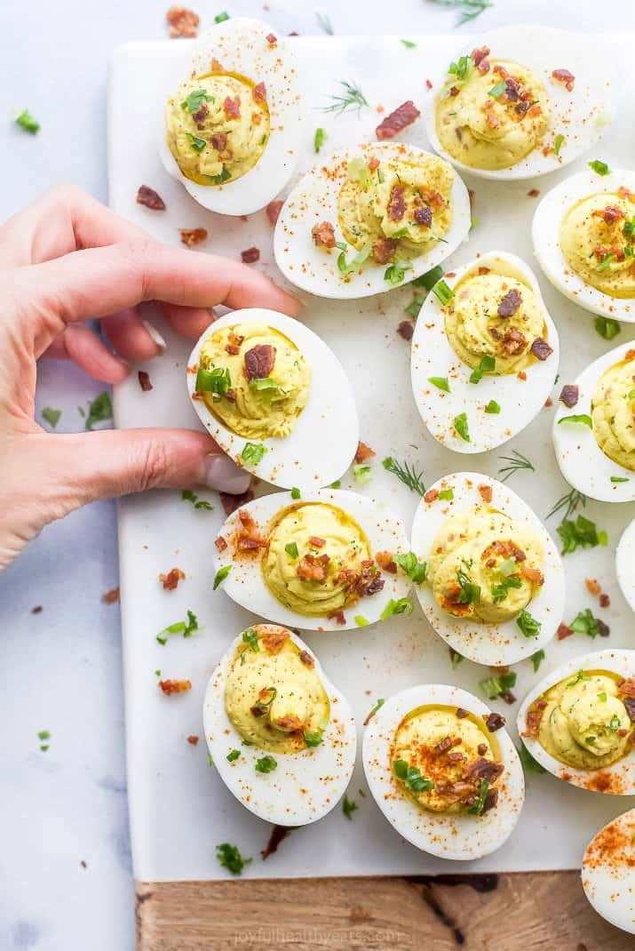 a hand grabbed a classic deviled egg with bacon