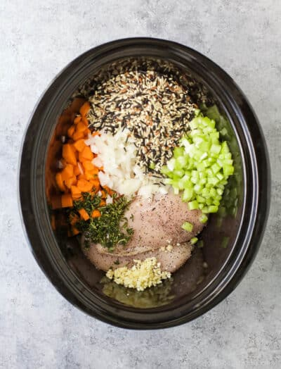 a crock pot full of ingredients for chicken and wild rice soup